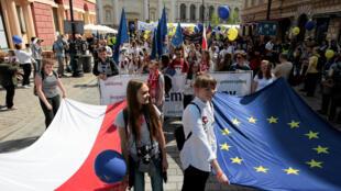 Des manifestants portent d'un même mouvement les drapeaux européens et polonais.