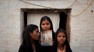 As filhas da paquistanesa Asia Bibi, com imagem da sua mãe, em frente ao local onde moravam na província de Punjab, em 13 de novembro de 2010.