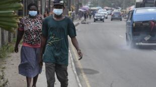 Les gens marchent le long d'une route principale portant des masques à Lagos, au Nigeria, le 28 février 2020.