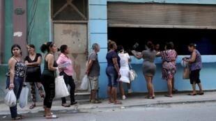 Des Cubains attendent en ligne pour acheter des marchandises dans un magasin d'État subventionné, à la Havane le 23 mars 2020.