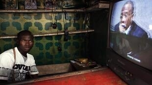 A street vendor in Freetown watches a live broadcast of the verdict convicting Charles Taylor of war crimes