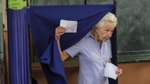 Une électrice grecque à la sortie de l'isoloir, dans un bureau de vote d'Athènes, lors du référendum de ce dimanche 5 juillet.