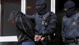 Policiais espanhóis levam algemado um dos dez militantes islâmicos detidos na manhã desta quarta-feira na região de Barcelona.