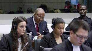 Former Liberian President Charles Taylor (rear L) sits next to a security guard as he waits for the start of a hearing