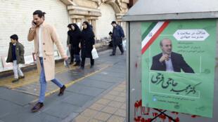 Des iraniens marchant à côté d'une affiche électorale des législatives du 21 février 2020