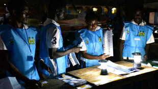 Election officials count ballot papers at a polling station in Freetown, 7 March 2018.
