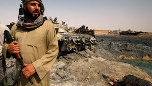 A rebel holds onto a weapon in front of tanks belonging to forces loyal to Libyan leader Moamar Kadhafi