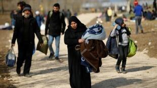 Les migrants marchent vers la frontière alors qu'ils se heurtent à la police anti-émeute grecque au poste-frontière turc de Pazarkule avec la Grèce Kastanies, près d'Edirne, le 6 mars 2020.
