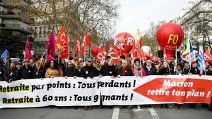 Public sector workers march in Paris against French President Emmanuel Macron's plans to reform the country's pension system, 10 December 2019.