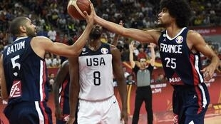 France's Nicolas Batum (L) and Louis Labeyrie handle the ball as Harrison Barnes (C) of the US watches during the Basketball World Cup quarter-final game between US and France in Dongguan on September 11, 2019.