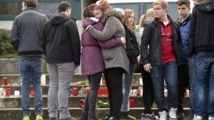 德國杜塞爾多夫一所高中有16名學生可能罹難,當地居民點燃蠟燭相擁而泣。