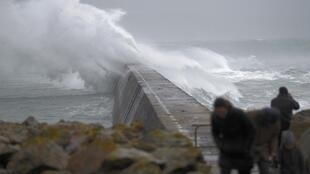 Waves crash over the breakwater of Saint Evette harbour at Esquibien in Brittany