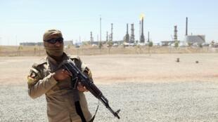Nhân viên an ninh người Kurdistan canh gác lối vào một khu nhà máy lọc dầu ở Mossoul, 22/06/2014