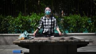 Una mujer con mascarilla se relaja tras haber practicado ejercicio en unos jardines de Pekín el 3 de abril de 2020