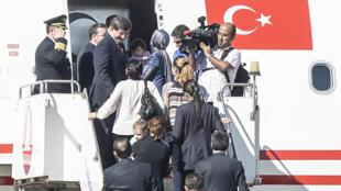 O primeiro-ministro turco Ahmet Davutoglu embarca em seu avião com os réfens libertados neste sábado (20), na fronteira entre a Turquia e a Síria.