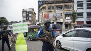 Une série d'attentats à la bombe visant des églises et des hôtels de luxe avait secoué le Sri Lanka, le dimanche de Pâques. Des soldats sri-lankais contrôlent leurs positions à un poste de contrôle à Colombo le 27 avril 2019