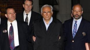 O diretor-gerente do Fundo Monetário Internacional, Dominique Strauss-Kahn sendo escoltado por policiais na saída da delegacia de Nova Iorque.