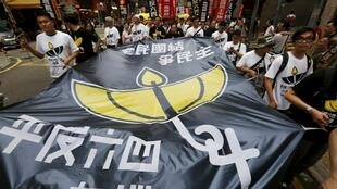 "Pro-democracy protesters carry a banner featuring an illustration ""64"", referring to June 4th, and a yellow umbrella, symbol of the Occupy Central movement, during a demonstration in Hong Kong, China May 31, 2015."