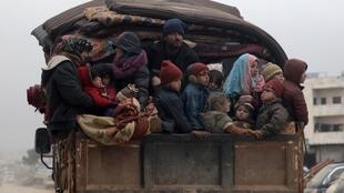 Internally displaced Syrians from western Aleppo countryside, ride on the back of a truck with belongings in Hazano near Idlib, Syria, February 11, 2020.