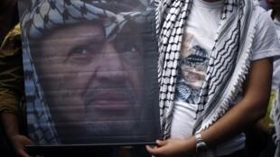 Un partisan du Fatah montre un poster à l'image de Yasser Arafat à l'université Al-Azhar de Gaza, le 11 novembre 2014, à l'occasion du 10e anniversaire de la mort du leader palestinien.