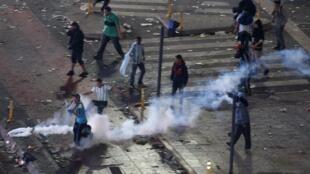 Confronto entre policiais e torcedores no centro de Buenos na madrugada desta segunda-feira (14); após a derrota na final da Copa do Mundo, alguns torcedores promoveram atos de vandalismo na capital artentina.