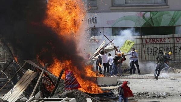 Protesters standing behind a barricade clash with riot police during a protest at Taksim Square in Istanbul, 11 June 2013