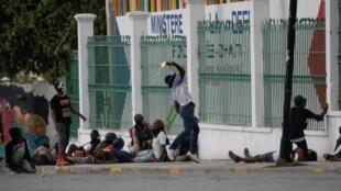 Un manifestant lance lance un cocktail molotov en direction du stand du ministère de la Défense installé sur le Champs de Mars pour le carnaval de Port-au-Prince.