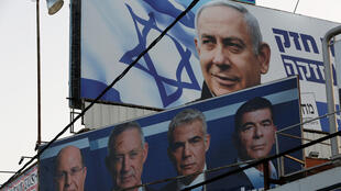 A Likud party election campaign billboard depicting Israeli Prime Minister Benjamin Netanyahu seen above a billboard depicting Benny Gantz, leader of Blue and White party
