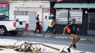 A French gendarme  chases off looters in Saint-Martin on 8 September