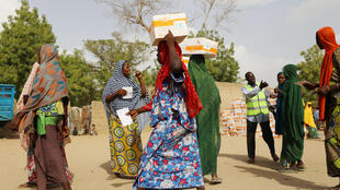 Women carry food supplement received from World Food Programme (WFP) at the Banki IDP camp, in Borno, Nigeria April 26, 2017. Picture taken April 26, 2017.