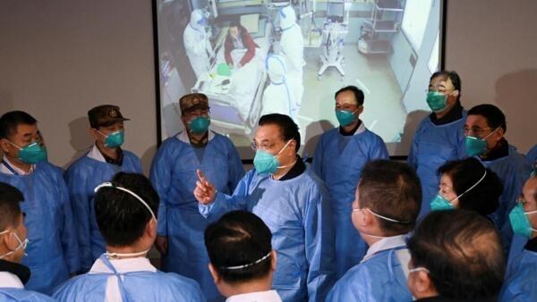 Thủ tướng Trung Quốc Lý Khắc Cường đeo mặt nạ và bộ đồ bảo hộ nói chuyện với các nhân viên y tế tại một bệnh viện có bệnh nhân nhiễm virus ở Vũ Hán, ngày 27/01/2020.