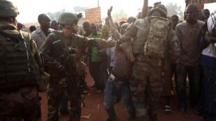 Militares franceses tratan de controlar a manifestantes que solicitan  la neutralización de grupos armados en las cercanías del aeropuerto de Bangui, el 23 de diciembre de 2013.
