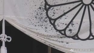 """一名中國男子手持裝有墨汁的塑料瓶進入靖國神社拜殿後潑灑。圖為一些墨汁潑灑到被叫做""""禦文章付白幕""""的帷幕上。"""