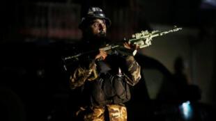 Um membro das forças de segurança defendendo o edíficio governamental atacado ontem em Cabul.
