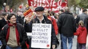 """Um homem segura um cartaz que diz """"Vovô e vovó no trabalho e jovens desempregados, não, obrigado"""". Manifestação em Paris, contra a reforma do sistema da previdencia. 19/10/10"""