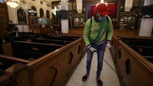 Des volontaires vaporisent un désinfectant à l'intérieur d'une église alors que l'Égypte ferme ses églises et mosquées en raison du Covid-19, au Caire, le 4 avril 2020.