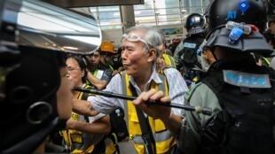"""""""Papy Wong"""" (G), 85 tuổi, dùng gậy che chắn người biểu tình trước cảnh sát, cùng với đội quân """"tóc bạc"""" ở quận Đông Dũng (Tung Chung), Hồng Kông ngày 07/09/2019."""