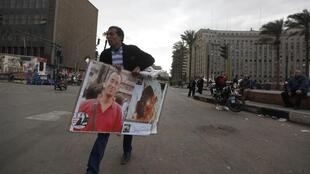 A protester carries pictures of journalist Al-Hosseiny Abu Deif at Tahrir Square, 21 December, 2012
