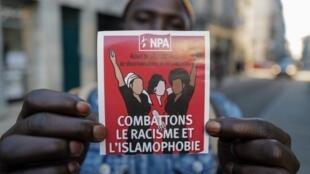 """Активист с плакатом """"Остановим исламофобию и расизм"""""""