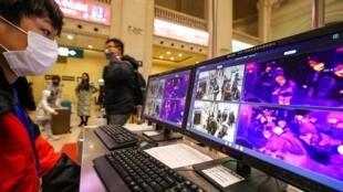 Surveillance des scanners thermiques qui détectent les températures des passagers lors du contrôle de sécurité à l'intérieur de la gare de Hankou à Wuhan, dans la province du Hubei, en Chine, le 21 janvier 2020.