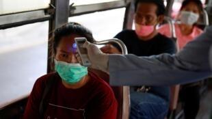 Un responsable sanitaire prend la température d'une passagère dans un bus, à Bangkok, le 26 mars 2020.