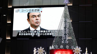 A street monitor showing a news report about arrest of Nissan Chairman Carlos Ghosn is seen next to Christmas illuminations in Tokyo, Japan November 21, 2018.
