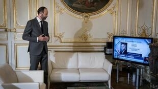 Prime Minister Edouard Philippe watches Interior Minister Richard Ferrand on television last month
