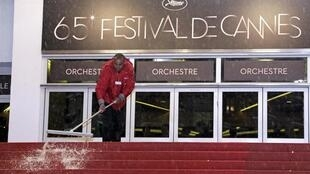 A man wipes water off the red carpet after freak storm ripped through festival
