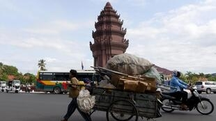 A Cambodian trader pulls his cart loaded with recyclable materials past the Independence monument in Phnom Penh on October 17, 2019.