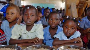 En Haïti, dans une école de la banlieue de Ganthier, le Programme alimentaire mondial (PAM) distribue de la nourriture aux enfants, le 12 novembre 2009.