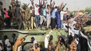 Des manifestants opposés au président Omar el-Béchir ont rejoint des militaires sur leurs véhicules blindés, jeudi 11 avril 2019 à Khartoum.