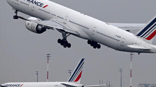An Air France Airbus Boeing 777 airplane takes off past a control tower at the Charles-de-Gaulle airport in Roissy, near Paris, France.