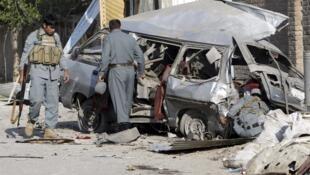 Полицейские осматривают остатки взорванного талибами микроавтобуса, в котором погибли 3 их коллег. Джалалабад 21/04/2011