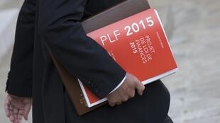 A minister leaves last week's cabinet meeting with a press release about France's 2015 budget